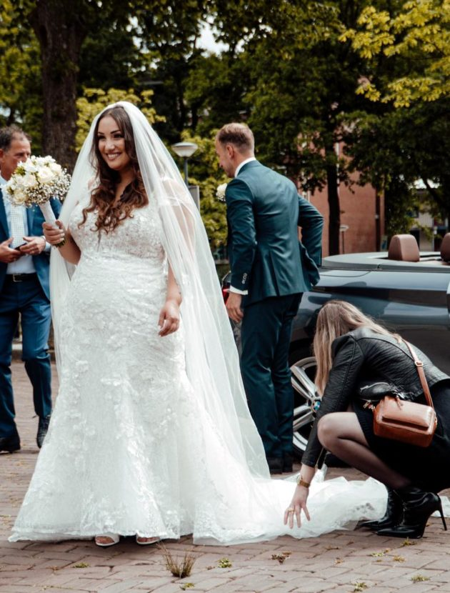 Prachtige plus size aansluitende ivoorkleurige trouwjurk met bijpassende sluier van Randy Fenoli
